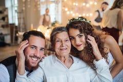 Młoda para z babcią na ślubie, patrzeje kamerę fotografia stock