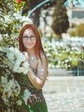 Młoda piękna ładna kobieta z czerwonym włosy i szkłami pozuje w kwiatu ogródzie, Roma, Włochy zdjęcie stock