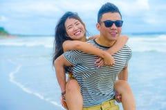 Młoda piękna Azjatycka Chińska para z chłopaka przewożenia kobietą na ona i ramiona przy plaży ono uśmiecha się z powrotem obraz royalty free