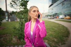 Młoda piękna biznesowa kobieta opowiada na telefonie poj?cia prowadzenia domu posiadanie klucza z?oty si?gaj?cy niebo obraz royalty free