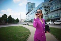 Młoda piękna biznesowa kobieta opowiada na telefonie poj?cia prowadzenia domu posiadanie klucza z?oty si?gaj?cy niebo obrazy royalty free