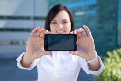 Młoda piękna biznesowa kobieta pokazuje smartphone z pustego miejsca scr Zdjęcie Royalty Free