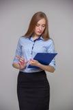 Młoda piękna biznesowa kobieta trzyma, myśleć na szarym tle i dokumentu pióro i pastylkę zdjęcie royalty free