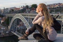 Młoda piękna blondynka siedzi naprzeciw Dom Luis przerzucam most przez Douro rzekę w Porto Obraz Stock