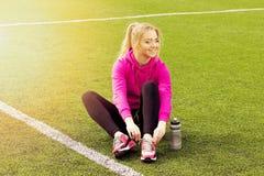 Młoda piękna blondynka włosy sprawności fizycznej dziewczyna wiąże shoelaces na stadium Lato bawi się aktywność Zielona stadium t Zdjęcie Stock