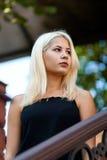 Młoda piękna blondynki dziewczyna pozuje na tle miastowy krajobraz Seksowna dama w czarnej sukni z przyjemnym zdjęcie stock