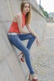 Młoda piękna blondynki dziewczyna w czerwony lato cajgów i bluzki pozować elastyczny Zdjęcia Royalty Free