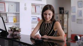 Młoda piękna brunetka, płaci kredytową kartą Kosmetologii klinika zbiory wideo