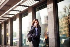 Młoda piękna brunetka pije kawowego odprowadzenie wokoło miasta skórzana kurtka, miastowy plecak, jaskrawe czerwone wargi Obrazy Stock
