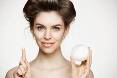 Młoda piękna brunetki dziewczyna ono uśmiecha się w włosianych curlers patrzejący kamerę creaming twarz nad białym tłem facial obrazy royalty free