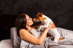 Młoda piękna brunetki kobieta bawić się w łóżku z jej psem Obraz Royalty Free