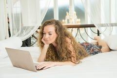 Młoda piękna caucasian kobieta kłaść na łóżku i używa laptop Fotografia Royalty Free