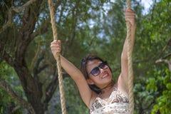 Młoda piękna Chińska Azjatycka dziewczyna ma zabawę na plażowego drzewa huśtawkowym cieszy się szczęśliwym uczuciu w wakacje letn Fotografia Stock
