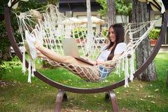 Młoda piękna ciemnowłosa kobieta w hamaku z laptopem Zdjęcia Royalty Free