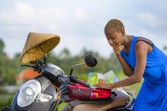 Młoda piękna czarna afro amerykańska turystyczna kobieta patrzeje drogowa mapa szuka sposób bada pola wewnątrz z hulajnoga motocy Obrazy Royalty Free