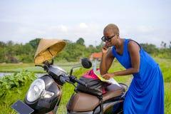 Młoda piękna czarna afro amerykańska turystyczna kobieta patrzeje drogowa mapa szuka sposób bada pola wewnątrz z hulajnoga motocy Obraz Stock