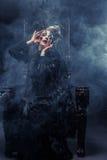 Młoda piękna czarownica siedzi na krześle Jaskrawy uzupełniał, czaszka, dymu Halloween temat Fotografia Royalty Free