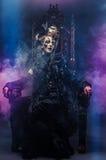 Młoda piękna czarownica siedzi na krześle Jaskrawy uzupełniał, czaszka, dymu Halloween temat Zdjęcie Stock