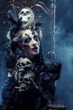 Młoda piękna czarownica siedzi na krześle Jaskrawy uzupełniał, czaszka, dymu Halloween temat Zdjęcie Royalty Free