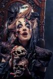 Młoda piękna czarownica siedzi na krześle Jaskrawy uzupełniał, czaszka, dymu Halloween temat Obrazy Royalty Free