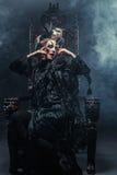Młoda piękna czarownica siedzi na krześle Jaskrawy uzupełniał, czaszka, dymu Halloween temat Obraz Royalty Free