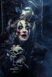Młoda piękna czarownica siedzi na krześle Jaskrawy uzupełniał, czaszka, dymu Halloween temat Zdjęcia Royalty Free