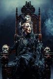 Młoda piękna czarownica siedzi na krześle Jaskrawy uzupełniał, czaszka, dymu Halloween temat Zdjęcia Stock