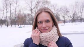 Młoda piękna długie włosy kobieta stoi w zimy miasta parku ono uśmiecha się przy kamerą z białym trykotowym szalikiem który i zdjęcie wideo