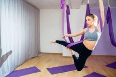 Młoda piękna dziewczyna ćwiczy powietrzny joga w gym Fotografia Stock