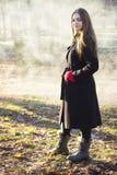 Młoda piękna dziewczyna bada wiosna lasu dymu parka w czarnego żakieta czerwonych rękawiczkach fotografia royalty free
