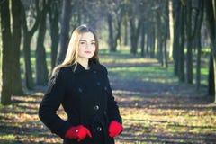 Młoda piękna dziewczyna bada wiosna lasu dymu parka w czarnego żakieta czerwonych rękawiczkach fotografia stock