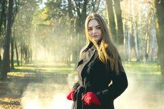 Młoda piękna dziewczyna bada wiosna lasu dymu parka w czarnego żakieta czerwonych rękawiczkach zdjęcia stock