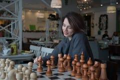 Młoda piękna dziewczyna bawić się szachy w kawiarni zdjęcia royalty free