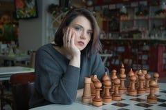 Młoda piękna dziewczyna bawić się szachy w kawiarni fotografia stock