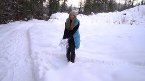 Młoda piękna dziewczyna chodzi w śnieżnym zima lesie jest szczęśliwa i rozochocona Dziewczyna rzuca śnieg swobodny ruch zbiory wideo