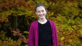 Młoda piękna dziewczyna chodzi w jesień lesie jest szczęśliwa Dziewczyna jest przyglądająca ono uśmiecha się i kamera zbiory