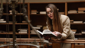 Młoda piękna dziewczyna czyta książkę w bibliotece obraz stock