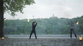 Młoda piękna dziewczyna i przystojny mężczyzna w czerni ubraniach wykonuje przedstawienie z płomień pozycją na riverbank zbieraj? zbiory wideo