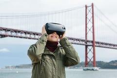 Młoda piękna dziewczyna jest ubranym rzeczywistość wirtualna szkła 25th Kwietnia most w Lisbon w tle Pojęcie Obrazy Royalty Free