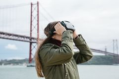 Młoda piękna dziewczyna jest ubranym rzeczywistość wirtualna szkła 25th Kwietnia most w Lisbon w tle Pojęcie Zdjęcie Royalty Free