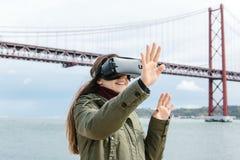 Młoda piękna dziewczyna jest ubranym rzeczywistość wirtualna szkła 25th Kwietnia most w Lisbon w tle Pojęcie Fotografia Royalty Free