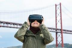 Młoda piękna dziewczyna jest ubranym rzeczywistość wirtualna szkła 25th Kwietnia most w Lisbon w tle Pojęcie Zdjęcie Stock