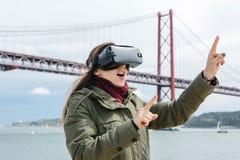 Młoda piękna dziewczyna jest ubranym rzeczywistość wirtualna szkła 25th Kwietnia most w Lisbon w tle Pojęcie Obraz Royalty Free