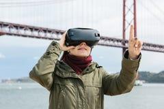 Młoda piękna dziewczyna jest ubranym rzeczywistość wirtualna szkła 25th Kwietnia most w Lisbon w tle Pojęcie Zdjęcia Royalty Free
