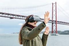 Młoda piękna dziewczyna jest ubranym rzeczywistość wirtualna szkła 25th Kwietnia most w Lisbon w tle Pojęcie Obraz Stock