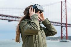 Młoda piękna dziewczyna jest ubranym rzeczywistość wirtualna szkła 25th Kwietnia most w Lisbon w tle Pojęcie Obrazy Stock
