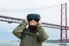 Młoda piękna dziewczyna jest ubranym rzeczywistość wirtualna szkła 25th Kwietnia most w Lisbon w tle Pojęcie Zdjęcia Stock