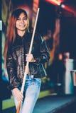 Młoda piękna dziewczyna jest ubranym skórzaną kurtkę w bilardowym klubie z wskazówka kija narządzaniem dla gry, Obrazy Royalty Free