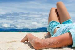 Młoda piękna dziewczyna kłama na białym piasku tropikalna plaża pod chmurnym niebem Obraz Stock