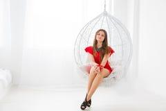 Młoda piękna dziewczyna odpoczywa w a jak dekoracyjna huśtawka w czerwieni sukni Elegancki i wygodny miejsce relaksować Zdjęcie Royalty Free